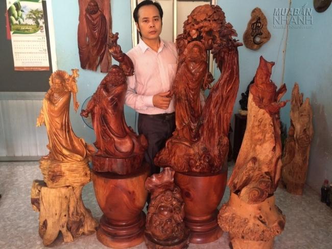 Nghệ nhân Nguyễn Quang Nam bên những tác phẩm tượng gỗ Đạt Ma Sư Tổ